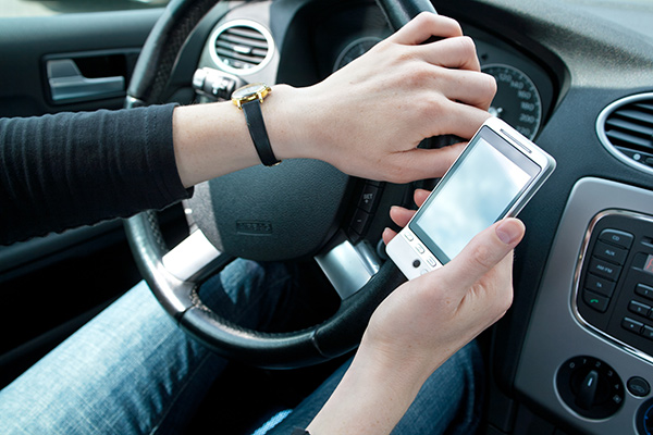 A driver looking at their smartphone while driving