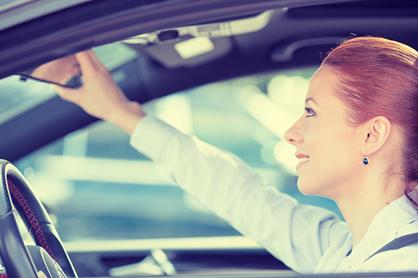 A woman adjusting her mirror, practicing safe driving habits on the road.