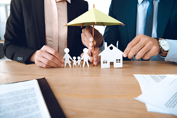 Insurance agents holding a small umbrella over paper cutouts of a family and home.