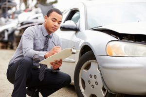 An insurance adjuster looking at the hood of a vehicle after an accident