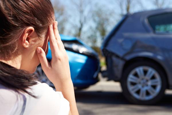 """A woman holds her hand to her temple and wonders, """"Does auto insurance cover rental cars?"""" as she looks at the damage from a rear-end collision."""